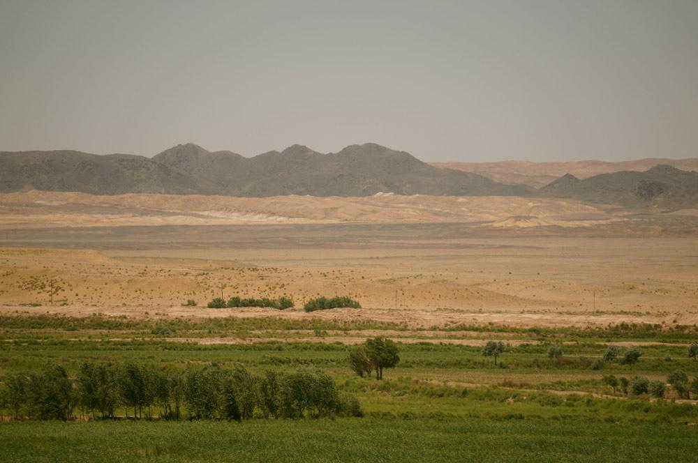 Widok z Toprak Kala na okoliczne pola oraz na góry Sultan Uvays Dag...